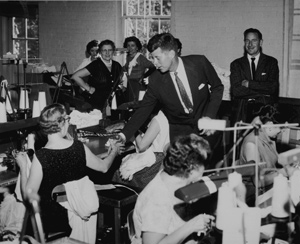 President John F. Kennedy shaking hands witha union worker in a factory