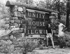 A man and a woman stand next to a sign for the ILGWU Unity House